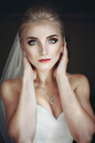 Beautiful innocent blonde bride with blue eyes posing, face clos Stock Image
