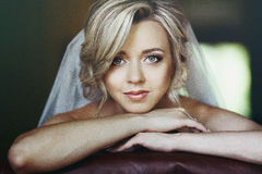 Beautiful innocent blonde bride leaning against chair closeup Stock Images