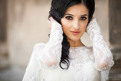 Beautiful innocent brunette bride in white dress posing near chu. Rch closeup Royalty Free Stock Images