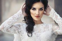 Beautiful innocent brunette bride in white dress posing near chu. Rch closeup Stock Photos