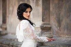 Beautiful innocent brunette bride in white dress posing near chu. Rch wall Stock Photos