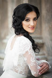 Beautiful innocent brunette bride in white dress posing near chu. Rch wall Stock Images