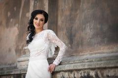 Beautiful innocent brunette bride in white dress posing near chu. Rch wall Royalty Free Stock Photos