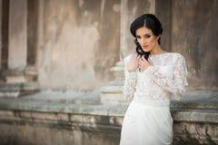 Beautiful innocent brunette bride in white dress posing near chu. Rch wall Stock Image