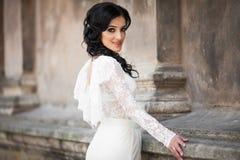 Beautiful innocent brunette bride in white dress posing near chu. Rch wall Stock Photography