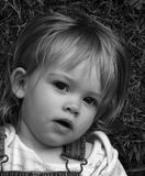 Beautiful Innocent Eyes. Daughter looking up from the grass with innocent eyes Stock Photos