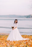 Beautiful innocent thoughtful bride in gorgeous white dress stands on fallen leaves at riverside Royalty Free Stock Image