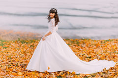 Beautiful innocent young brunette bride in gorgeous white dress stands on fallen leaves at riverside Stock Image