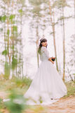 Beautiful innocent young brunette bride in gorgeous white dress stands on forest trail at sunny day Stock Images