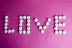 Beautiful inscription love made from white round smooth medical pills, vitamins, antibiotics and copy space on a bright purple royalty free stock image