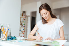 Beautiful inspired woman painter painting in art studio. Beautiful inspired woman painter sitting and painting in art studio Royalty Free Stock Photos