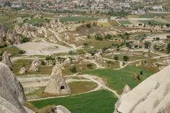Beautiful inspiring scenic panoramic landscape view of rock cave from red valley with Goreme town background, Cappadocia royalty free stock image