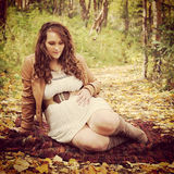 Beautiful instagram of pregnant woman sitting on forest path Royalty Free Stock Photo
