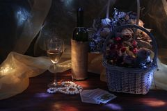 Still life with wine and flowers in the light of the moon royalty free stock image