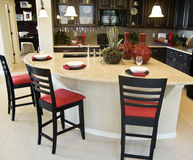 A beautiful interior of a custom kitchen. With island and bar stools Royalty Free Stock Photos
