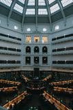 Beautiful interior of a large library with people working on laptops royalty free stock image