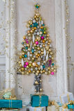 Beautiful interior living room decorated for Christmas. Big mirror frame with a tree made of balls and toys Stock Photo