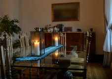 Beautiful interior of a room with a glass table on which stands the two candles burning lamps Royalty Free Stock Photo
