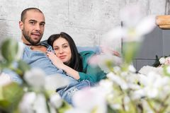 Beautiful international couple of man with beard and his brunette wife sitting in an embrace on the sofa royalty free stock images