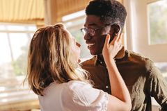 Beautiful interracial couple in love. Beautiful interracial couple looking each other with love while standing indoors. Romantic men and women embracing each stock images