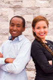 Beautiful interracial couple posing, rubbing shoulders and smiling for camera Royalty Free Stock Photography