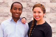 Beautiful interracial couple posing and smiling for camera, her hand on his shoulder Royalty Free Stock Photos