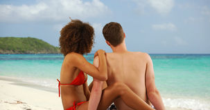 Beautiful interracial couple sitting on sand looking at tropical beach horizon. Stock Photo