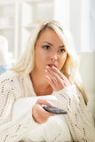Beautiful intrigued woman watching TV using remote control.  Royalty Free Stock Photos