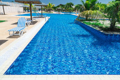 Beautiful inviting gorgeous view of swimming pool, tranquil turquoise azure water and tropical garden Stock Photography