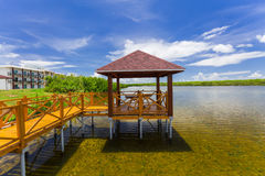 Beautiful inviting view of bridge leading to gazebo standing in water and resort hotel grounds Stock Photos