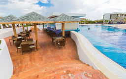 Beautiful inviting view of comfortable swimming pool and bar sitting area with people relaxing, swimming in background Stock Photography