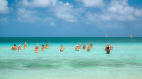 Beautiful inviting view of group of people enjoying their time by doing dancing water sport exercises in tranquil turquoise ocean Stock Photography