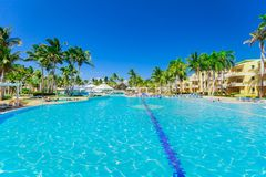 beautiful inviting view of hotel grounds and people relaxing in swimming pool royalty free stock images