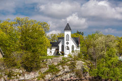 Beautiful inviting  view of old vintage white church standing on a rock cliff in woods Royalty Free Stock Image