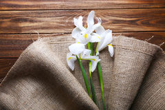 Beautiful irises wrapped in burlap fabric on wooden table, top v Stock Image