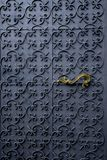 Iron door with golden handle. A close up of an old fashioned iron door with a golden handle royalty free stock image