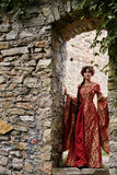 Beautiful Isabella of France, queen of England on Middle Ages period. In red gown near medieval castle stock photos