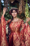 Beautiful Isabella of France, queen of England on Middle Ages period. In red gown near medieval castle royalty free stock photo