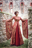 Beautiful Isabella of France, queen of England on Middle Ages period. In red gown near medieval castle Royalty Free Stock Photos