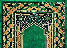 Beautiful Islamic praying rug pattern. Beautiful Islamic praying carpet or rug in pattern, ornaments seamless in green and golden can be used for decoration Royalty Free Stock Photo
