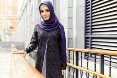 Beautiful Islamic woman in traditional oriental clothes standing on a city street royalty free stock photo