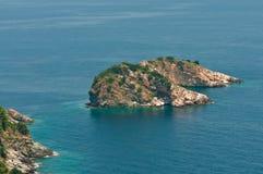 Beautiful island in a blue lagoon. Beautiful island with trees in a blue lagoon near the shore Royalty Free Stock Photography
