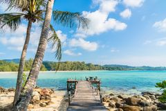 Coconut palm tree on the beach and sea. Beautiful island paradise with bridge and coconut palm tree around sea and beach on white cloud and blue sky - Holiday Royalty Free Stock Photo