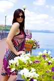 Beautiful italian woman posing in front of colored flowers and lake in vacation Stock Image