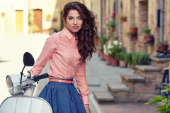 Beautiful italian woman sitting on a italian scooter. Stock Image