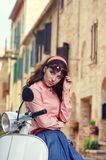 Beautiful italian woman sitting on a italian scooter. Royalty Free Stock Images