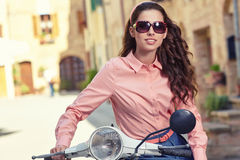 Beautiful italian woman sitting on a italian scooter. Royalty Free Stock Photo