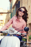 Beautiful italian woman sitting on a italian scooter. Stock Photos