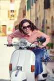 Beautiful italian woman sitting on a italian scooter. Stock Photography
