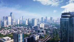 Beautiful Jakarta city under clear sky. JAKARTA - Indonesia. May 21, 2018: Beautiful scenery of Jakarta city with skyscrapers and residential house under clear Royalty Free Stock Images